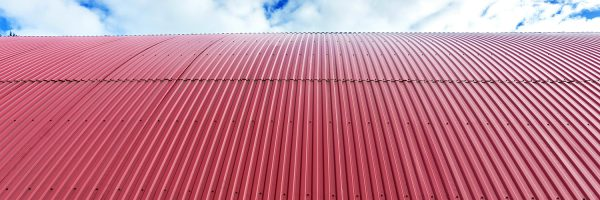 Rooftop of curved red corrugated iron on blue sky with fluffy clouds